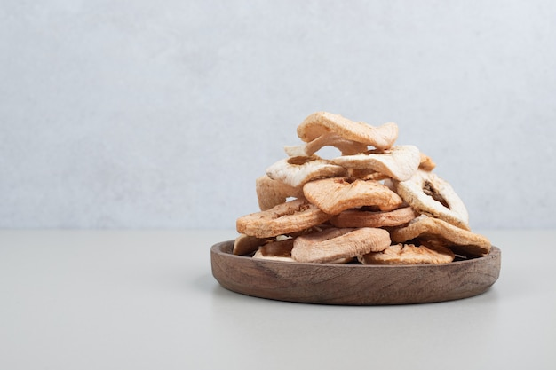 Dried apple chips on wooden plate