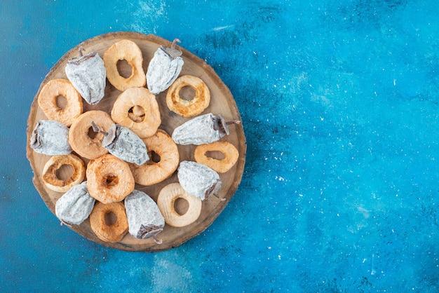 青い表面のボード上の乾燥リンゴリングと柿