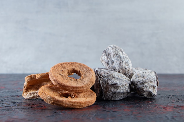 Dried apple rings and tasty persimmons on dark background.