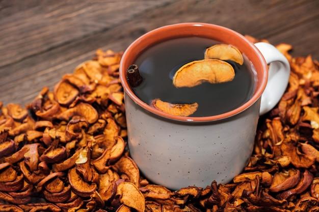 乾燥したリンゴのスライスがクローズアップされ、健康的な食事の飲み物に役立つビタミンです。 uzvarとカップ。