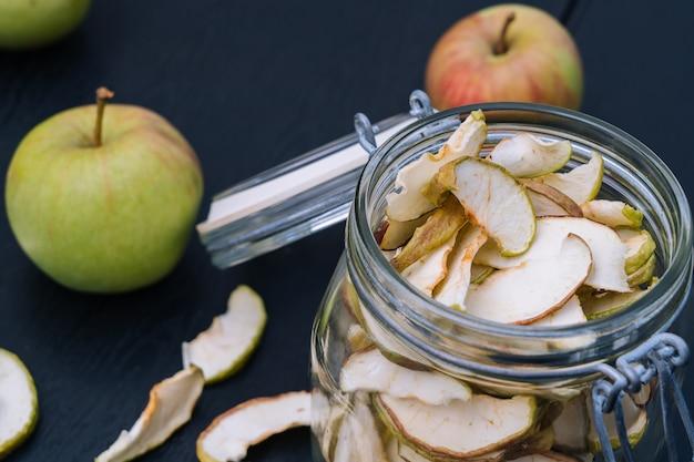 開いたガラスの瓶にリンゴのスライスを乾燥させます。黒いテーブル背景に新鮮なリンゴと自家製有機乾燥アップルチップ。