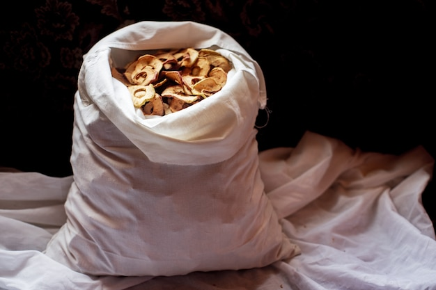 Dried apples in rings in a white bag on a dark background a healthy snack with vitamins
