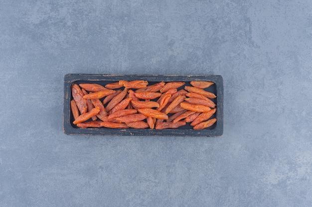 Сушеный абрикос в деревянной тарелке на мраморном фоне.