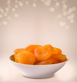 Dried apricot into a bowl on beige background.