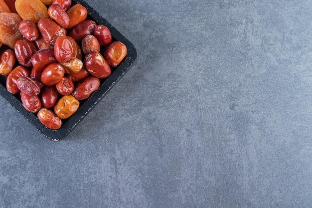 Albicocca secca e oliva su un tagliere, sul piano di marmo