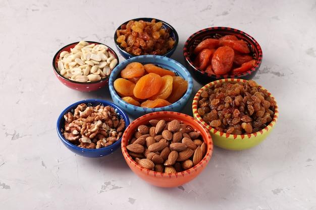Сушеный абрикос, изюм, арахис, миндаль, грецкий орех в мисках на сером бетонном пространстве, крупным планом
