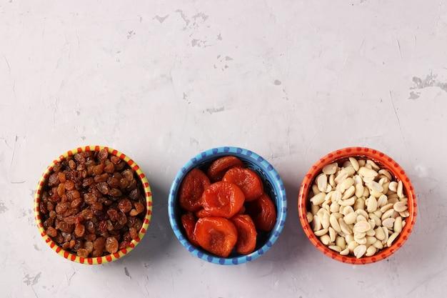 Сушеный абрикос, изюм, арахис в блюдцах, стоящих в ряд на сером пространстве. вид сверху. место для текста