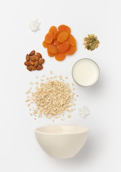 Dried apricots, almond, oat flakes and milk pours in ceramic bowl