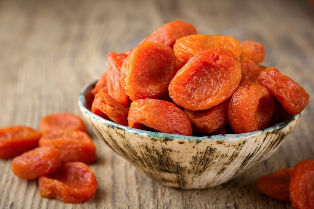 Dried apricots in a bamboo bowl on an old wooden. healthy dried fruit
