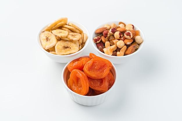 Сушеные абрикосы, банановые чипсы и смесь орехов в трех мисках на белой стене. здоровые закуски.