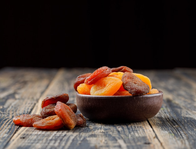 Dried apricots in a clay bowl on wooden table