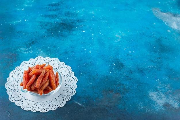 青いテーブルのコースターのボウルに干しあんず。