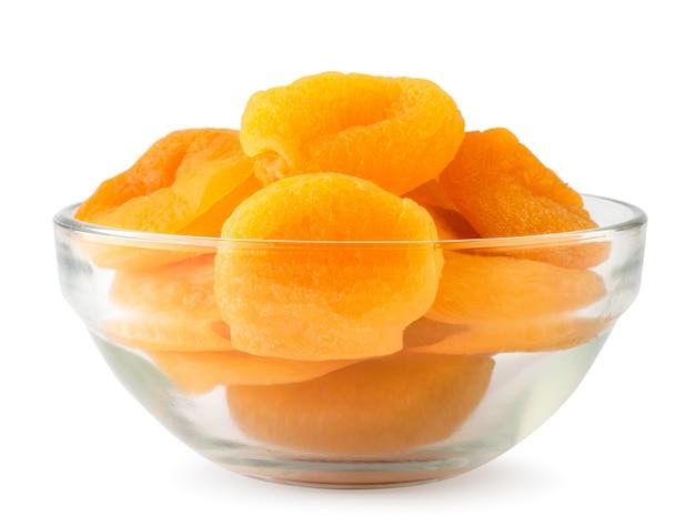 Сушеные абрикосы в стеклянной тарелке крупным планом изолированные