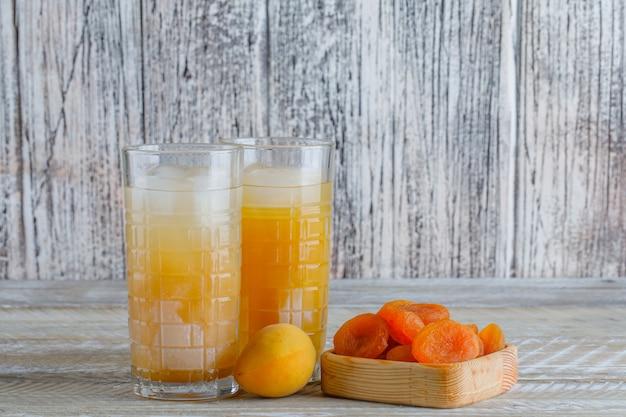 ジュース、木製のテーブルに新鮮なアプリコットの側面図と木の板でアプリコットを乾燥