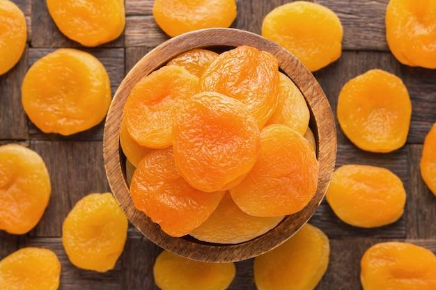 Сушеные абрикосы в шаре на фоне деревянного стола.