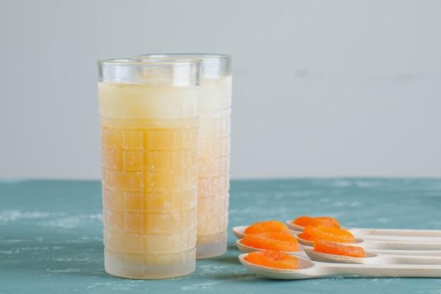 ジュースの側面図と木製のスプーンでアプリコットを乾燥