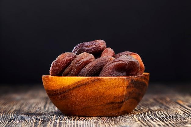 Курага из натуральных абрикосов, курага темного цвета, естественная сушка без применения ускорителей и ненатуральных химических элементов, сухофрукты на деревянном столе.