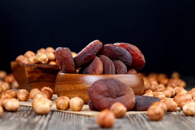 Курага из натуральных абрикосов, курага темного цвета, естественная сушка без использования ускорителей и ненатуральных химических элементов, сухофрукты на деревянном столе.