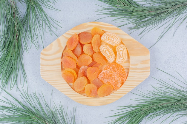 Dried apricots and marmalades on wooden plate.
