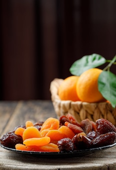 Dried apricots in a plate with dates and oranges in basket