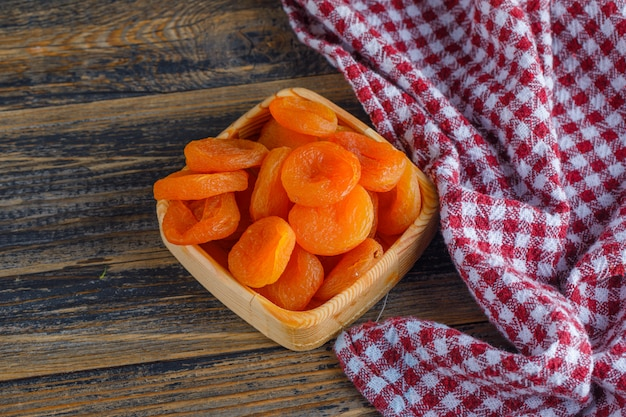 Dried apricots in a wooden plate on wooden and picnic cloth. .
