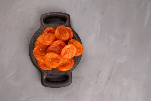 Dried apricots on wooden serving plate