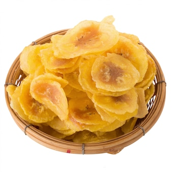 Dried banana chips in wooden bowl. yellow deep fried slices of bananas isolated on white background