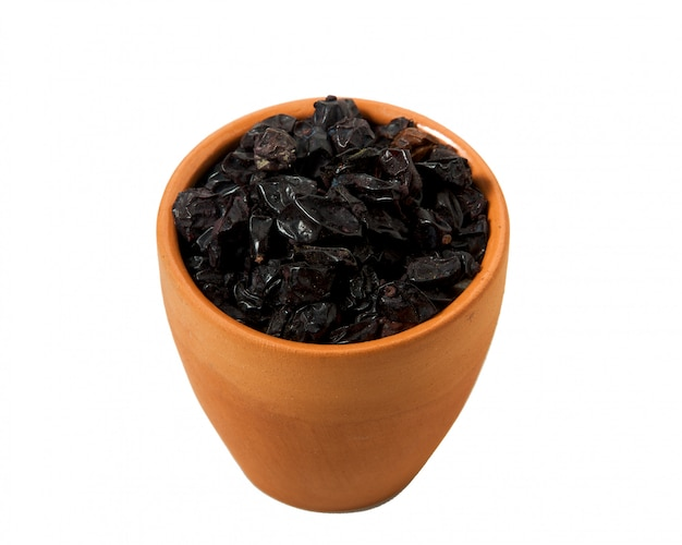 Dried barberry in an earthenware cup on a white background.