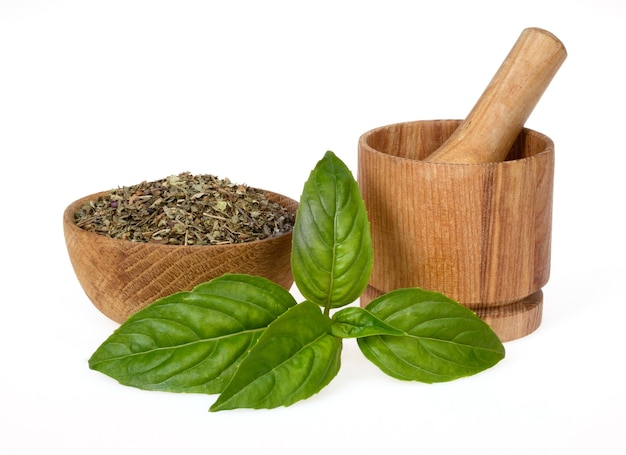 Dried basil crushed with green leaves in a wooden bowl and a mortar on a white background