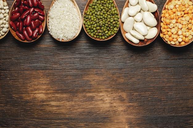 Сушеные бобы в деревянные ложки на столе, крупным планом