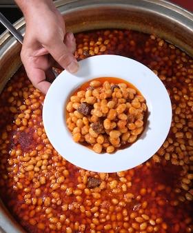 焼きたての鍋(トルコのクルファスリー)から皿に盛り付けた乾燥豆