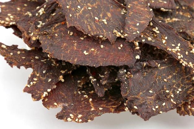 Сушеные кусочки говядины в специях с кунжутом. здоровое и витаминное питание