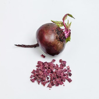 Dried beetroot and fresh vegetable lie on a white substrate