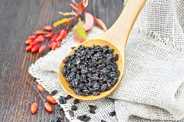 Dried black barberry in a spoon on sacking, sprigs with fresh berries and leaves on a wooden board background