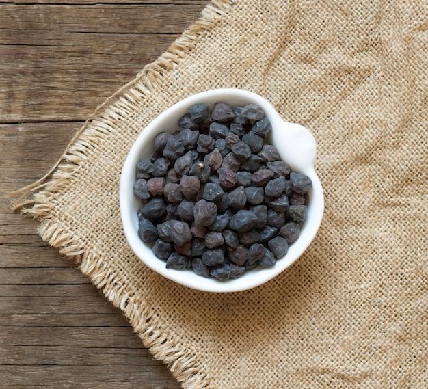 木製のテーブルトップビューで黄麻布のボウルに黒ひよこ豆を乾燥