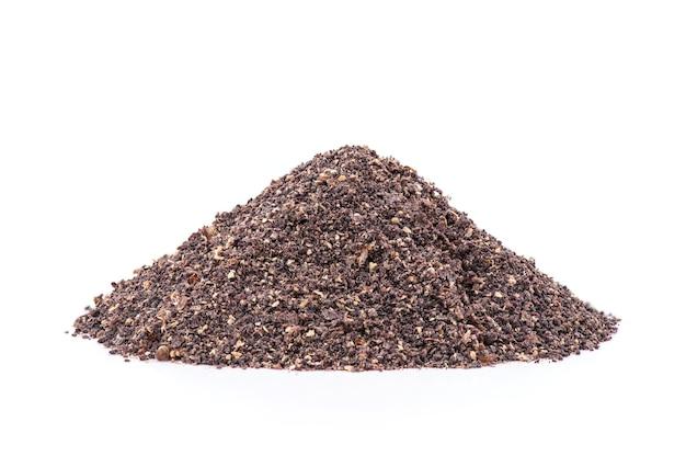 白い表面に分離された乾燥した黒いガランガル粉末。