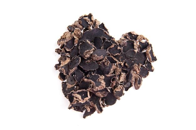 Сушеные ломтики черного галингала расположены в форме сердца на белом фоне. вид сверху, плоская планировка.