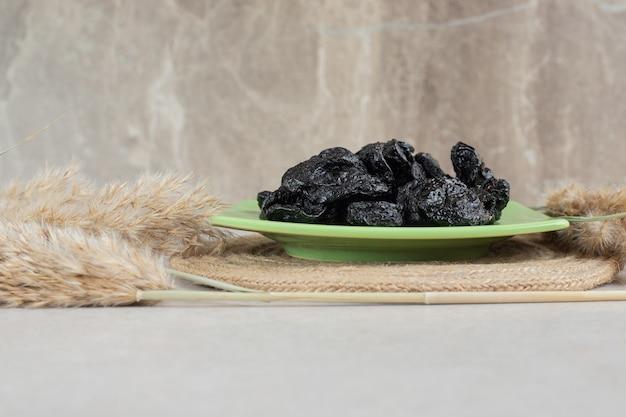 Prugne nere secche in un piatto di ceramica.