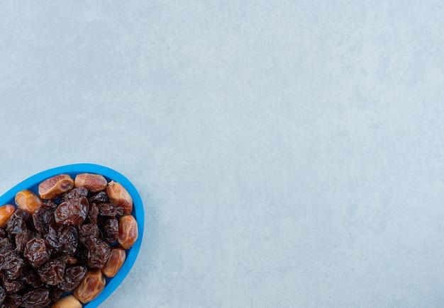 青い大皿にナツメの果実が入った乾燥した黒いプラム。高品質の写真