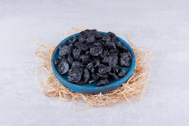 Dried black sultanas in a plate on concrete background. high quality photo