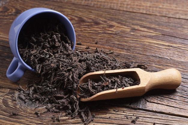 Dried black tea in blue cup and scoop old wooden table