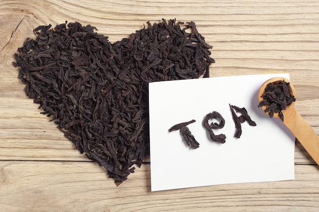 Dried black tea in the form of heart on wooden background, top view