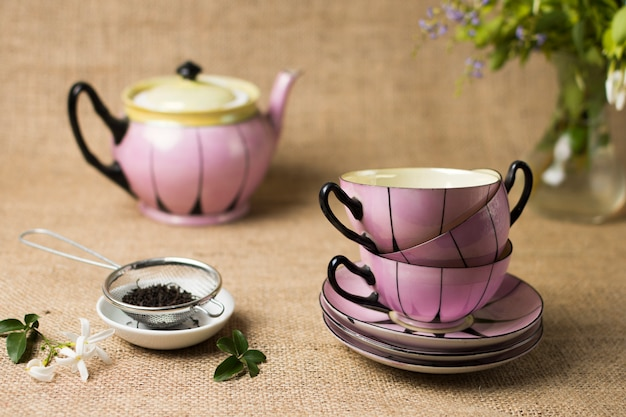 Dried black tea with flowers and stack of ceramic cup and saucers on jute tablecloth