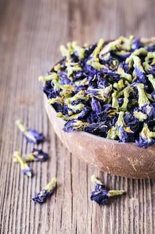 木製の背景に青い蝶エンドウ豆の花を乾燥させます。