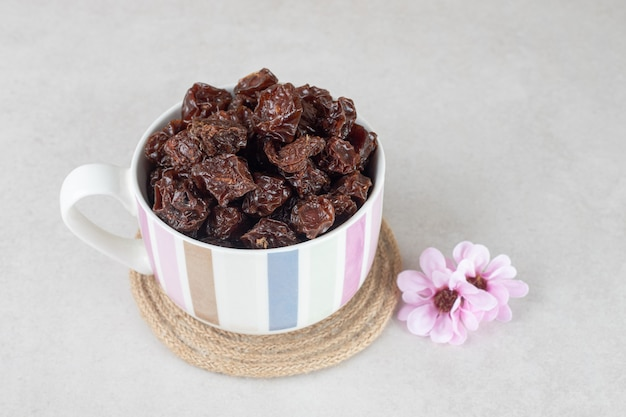 Dried brown plums in a ceramic cup.