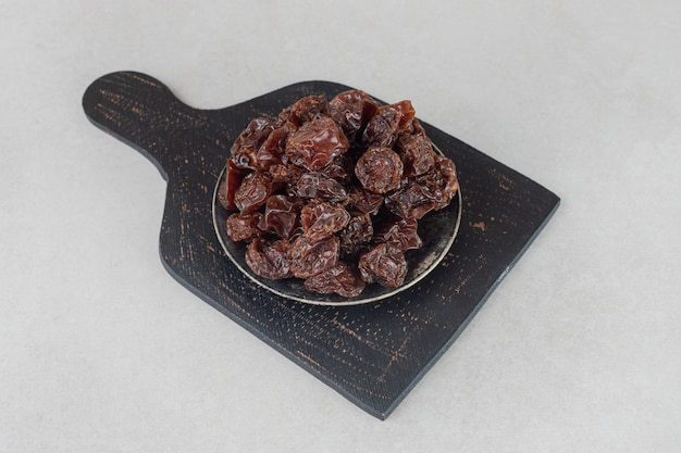 Dried brown plums on a wooden platter.