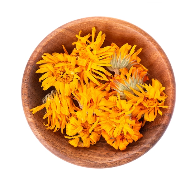 Dried calendula flowers in wooden bowl, isolated on white background. petals of calendula officinalis. medicinal herbs. top view.