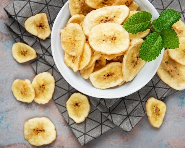 회색 콘크리트 표면에 말린 설탕에 절인 바나나 조각 또는 칩