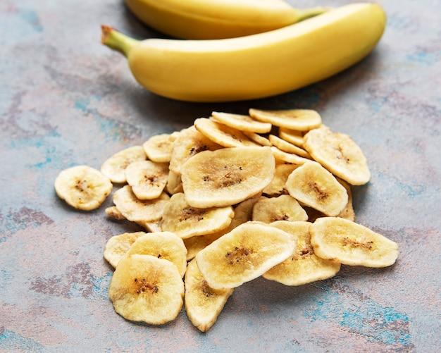 Сушеные засахаренные ломтики банана или чипсы на серой бетонной поверхности