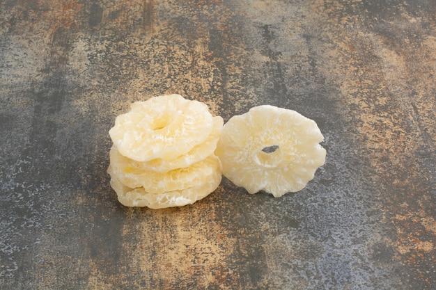 大理石の背景に乾燥した砂糖漬けのパイナップルリング。高品質の写真